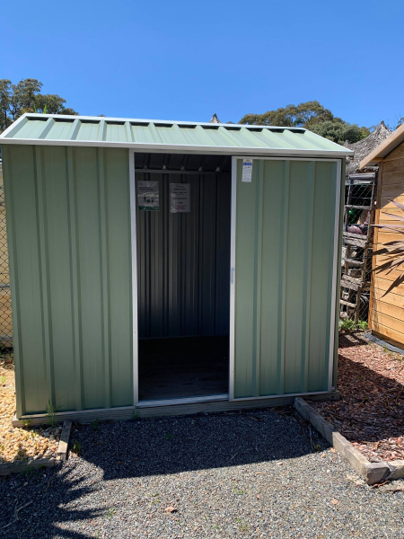 Small garden shed with sliding door in mist green.