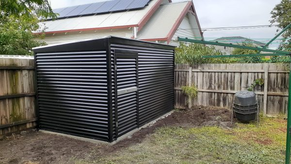 Garden shed with horizontal corrugated cladding.
