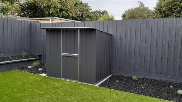 Garden shed hard against fence with extra roof overhang over door.
