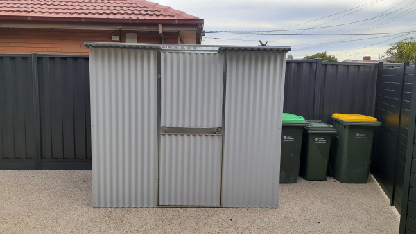 Shed on driveway against fence made from heavy duty corrugated steel.