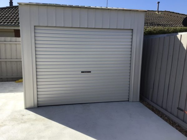 Roller Door Storage shed on concrete driveway.