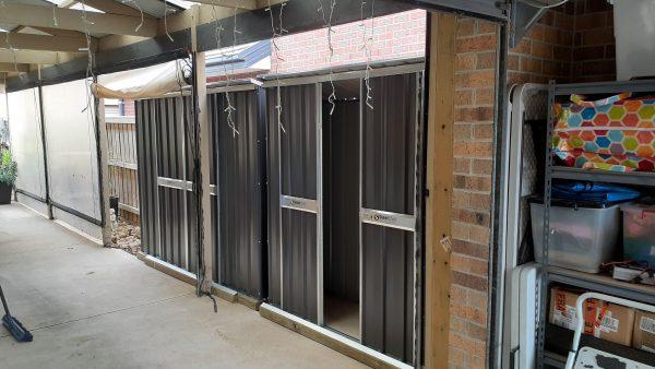 Slim storage sheds with sliding doors.